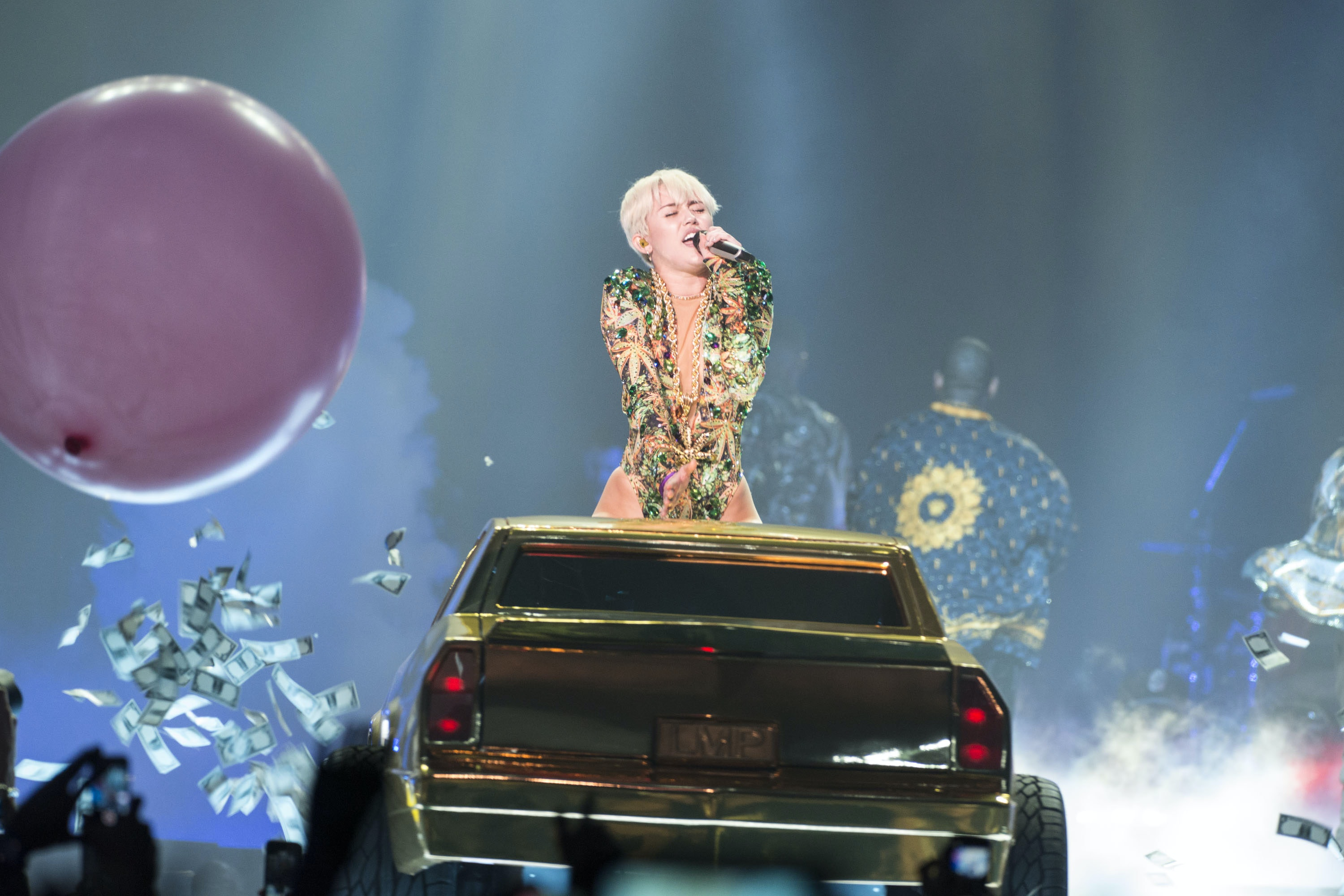 Miley, cyrus throws around paper money as she arrives